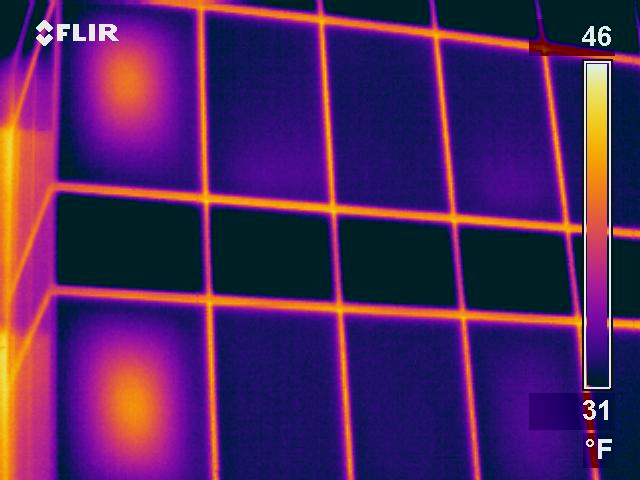 Thermogram shows warm thermal anomaly at the center of two IGU windows. Pattern typical of failed seals.